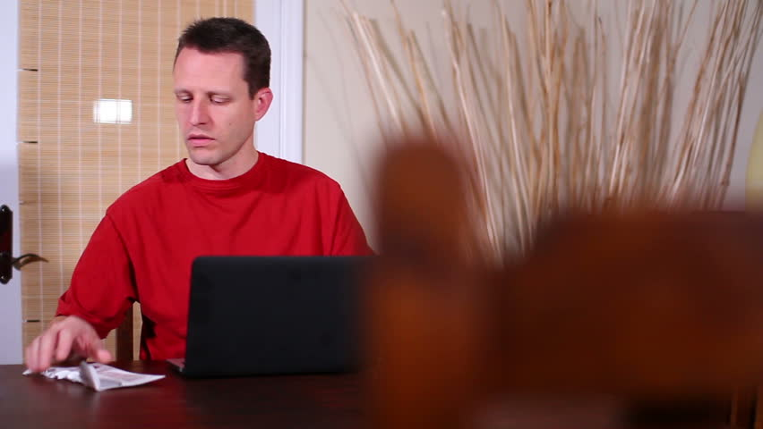A distraught man pays his bills.