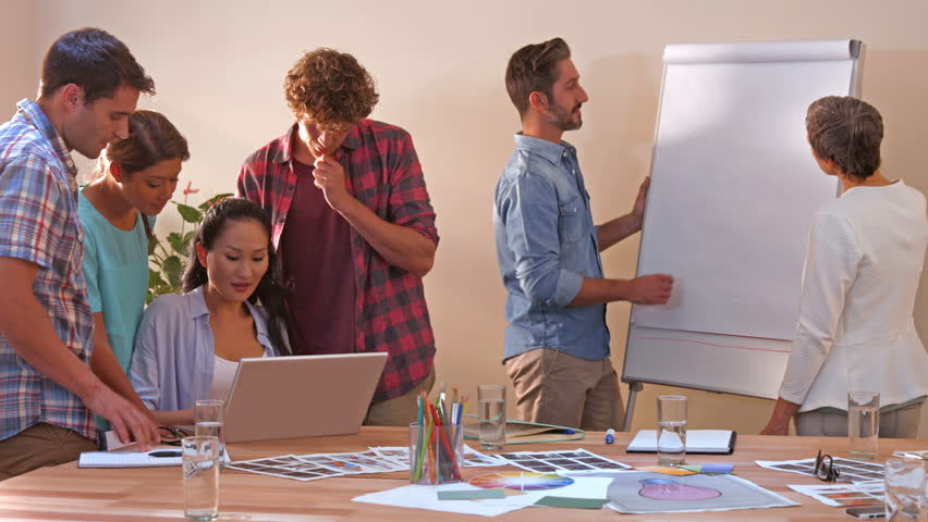 Creative business team working on laptop while their colleagues looking at white board in office | Shutterstock HD Video #14953876