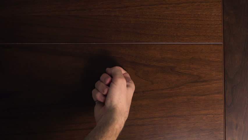 Male hand knocking at wooden door, visitor or guest at the door.