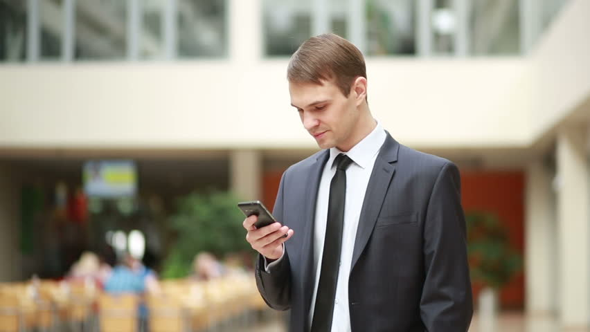 A young, handsome business man at the office building on phone | Shutterstock HD Video #14969782