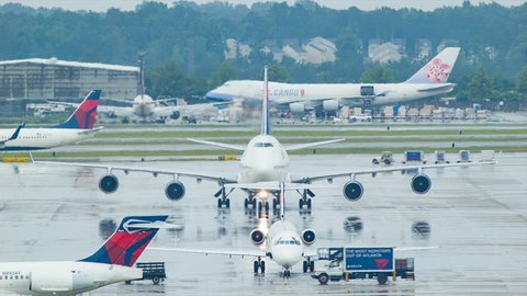 ATLANTA GA - 2015: Atlanta ATL Airport Delta Airlines Airplane Action with Boeing 747 and other Regional Jet Airplanes on Wet Platform