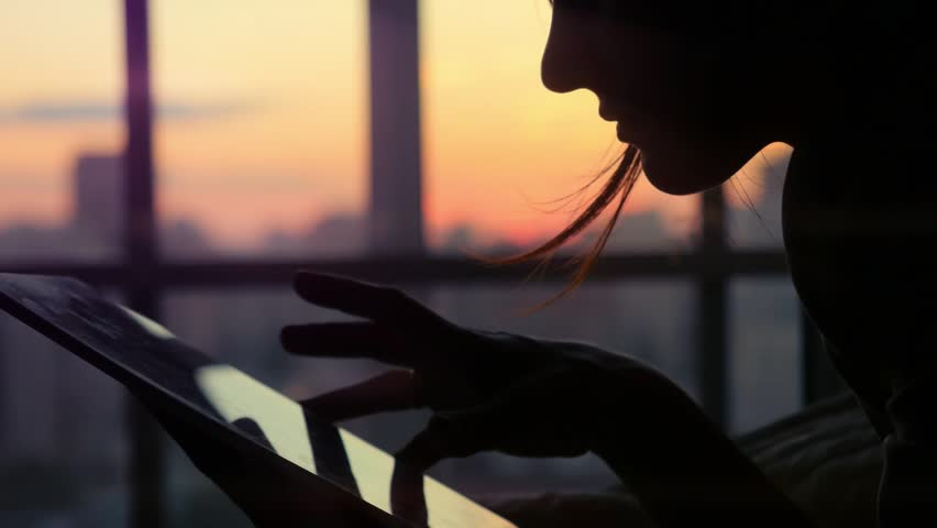 Woman using tablet with sunbeams and lens flare Business girl young adult against twilight sky window on bokeh blurred urban background. 1920x1080