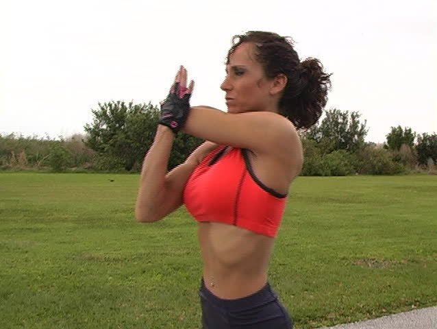 A pretty brunette in fitness wear, with remarkable muscle definition, stretches prior to jogging outdoors.  Camera mounted on fig rig; deliberate movement.