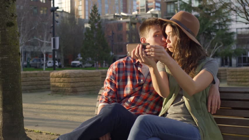 Video Bench Part - 40: Cute Couple Sit On A Bench And Take A Selfie Together, Woman Makes A Face