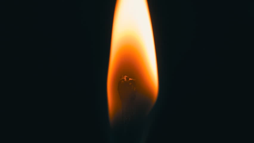 Head matches is lit a bright flame. The match stands upright. Closeup