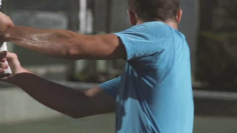 Tennis player hits the ball with backhand. Slow motion.