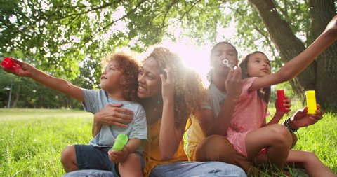 Young african-american family sitting and playing together in beautiful park blowing bubbles and laughing