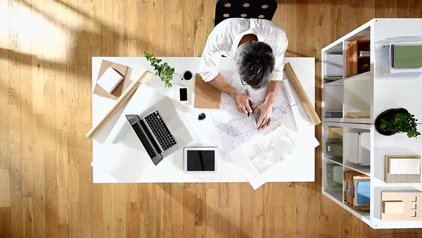 An Architect Sitting At His Desk And Working On A Building Project