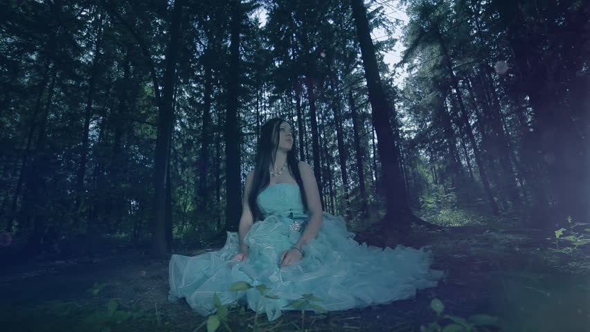 Fairy tale. The charming girl sitting in the fairy forest. (slow motion)