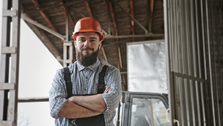 Portrait of cheerful bearded handsome young adult industrial engineer wear plastic helmet uniform against the background of loader. RAW video record.