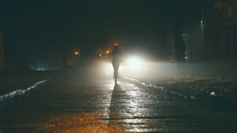 Girl at night is on the dangerous streets of the city on the car headlights.