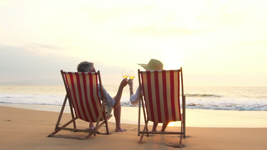 beautiful relaxing furniture. Slow Motion Retirement Vacation Concept  Happy Mature Retired Couple Enjoying Beautiful Sunset at the Beach Relaxing On Tropical Resort Luxury Chairs