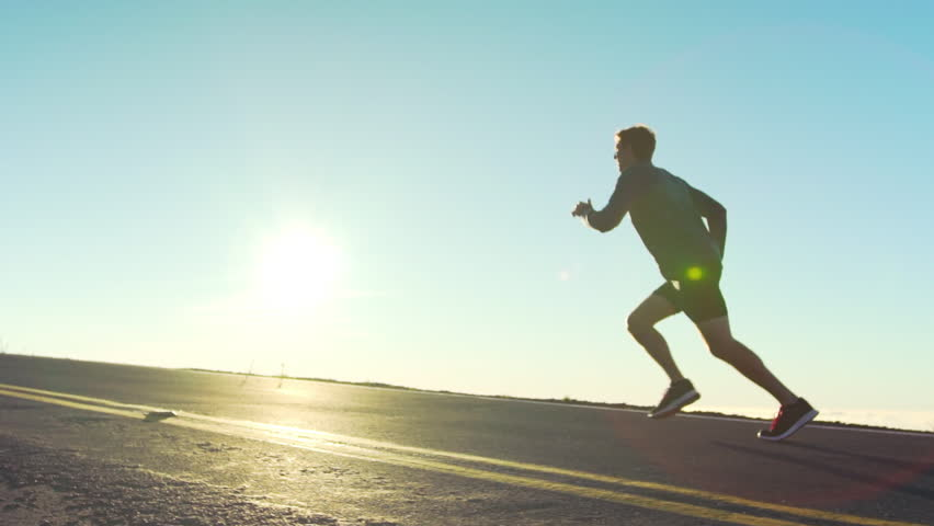 Slow Motion Male athlete exercising outdoors. Sports and active lifestyle. Male runner silhouette, Man running into sunset, colorful sunset sky.