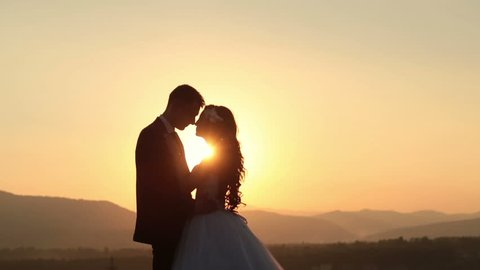Beautiful wedding couple kiss on the sunset in the mountains