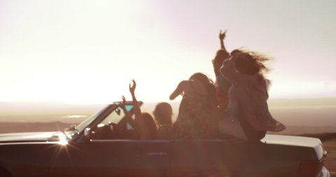 Excited group of young adult friends walking towards their vintage convertible car parked over wind farm at sunset during their road trip.