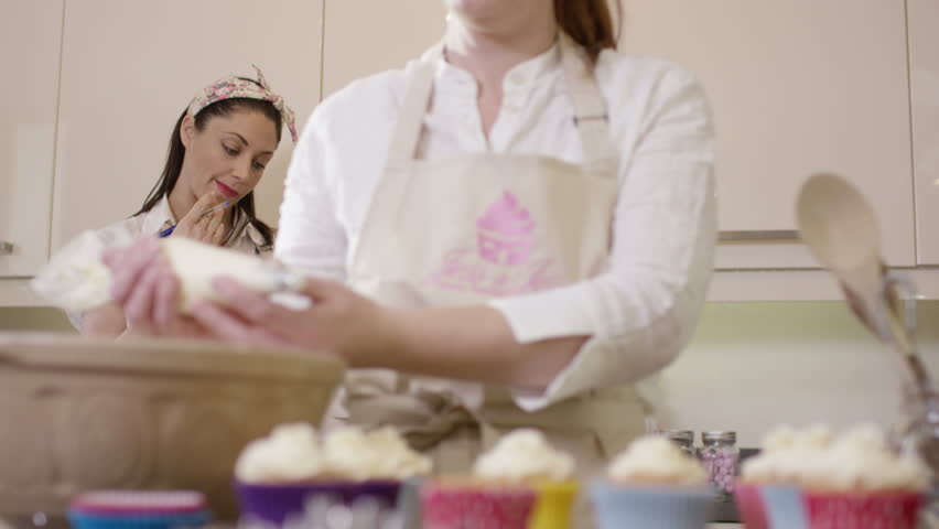 Woman Decorating Cupcakes 4k woman with home bakery business piping cream onto cupcakes