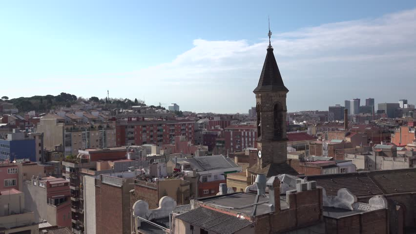 Catholic church bell tower stand above city roofs, Barcelona panorama at Hostafrancs area at Sants-Montjuic district. Daytime scene, crowded residential block surround old structure. Static camera.