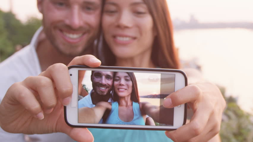 Couple taking selfie self portrait photo picture in Stockholm. Candid Scandinavian man and Asian woman looking at old town cityscape sunset view from Monteliusvagen overlooking Gamla Stan the old city | Shutterstock HD Video #15134872