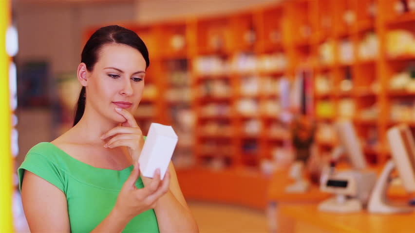 Pensive young woman looking at medical product in pharmacy