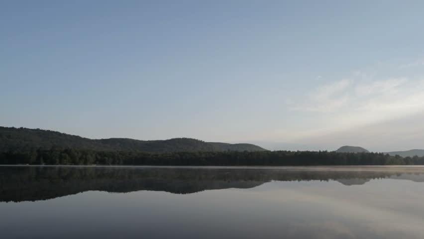dead calm water shows gentle rippling reflection of Adirondack mountains,Lows Lake, Adirondack state park,New York,USA.