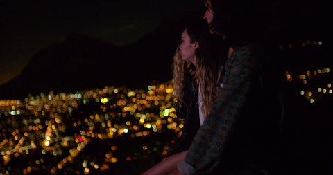 Back view of a group of friends hugging sitting on the bonnet of a car and watching night city lights from viewpoint