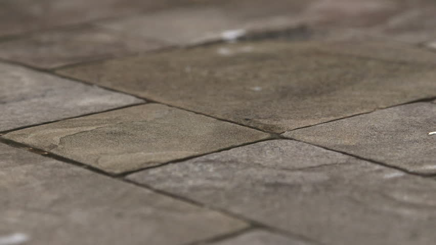Rain Drops Rippling In A Puddle On Wet Patio Garden Driveway Natural Stone  Paving Slab
