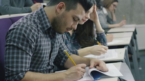 Footage of students writing with pens on paper in a collage classroom during lecture. Shot on RED Cinema Camera in 4K (UHD).