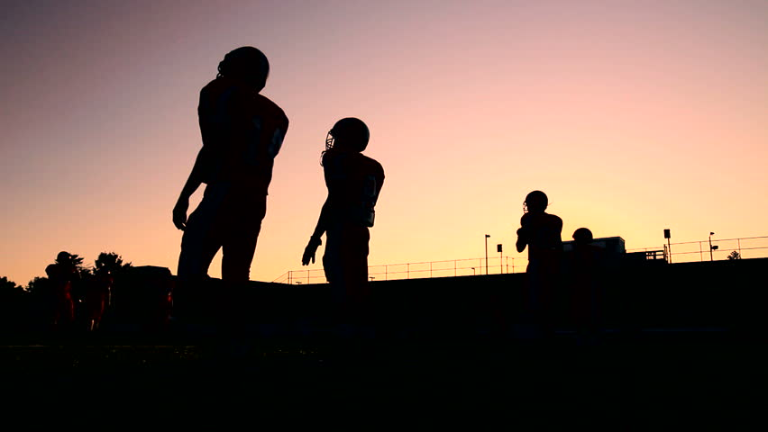 Football players warming up and having a catch