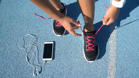 Closeup of feet of female runner getting ready tying running shoes with smartwatch, earphones and phone for music motivation for cardio workout training on athletic track in outdoor gym.