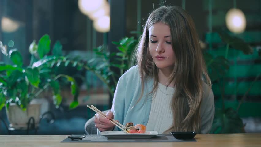 Girl enjoys rolls in Japanese restaurant