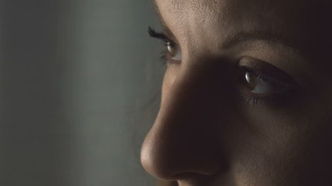 sad young woman opens eyes; sad and melancholy look, closeup portrait