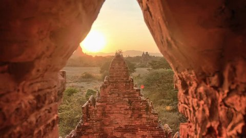 Sunset timelapse in Bagan, Myanmar. Dolly sliding along the walls of stupa/pagoda, and coming out of the brick door. Fast motion video of moving clouds.