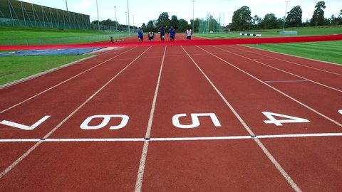 4K Drone footage of track athletes crossing finish line at running track