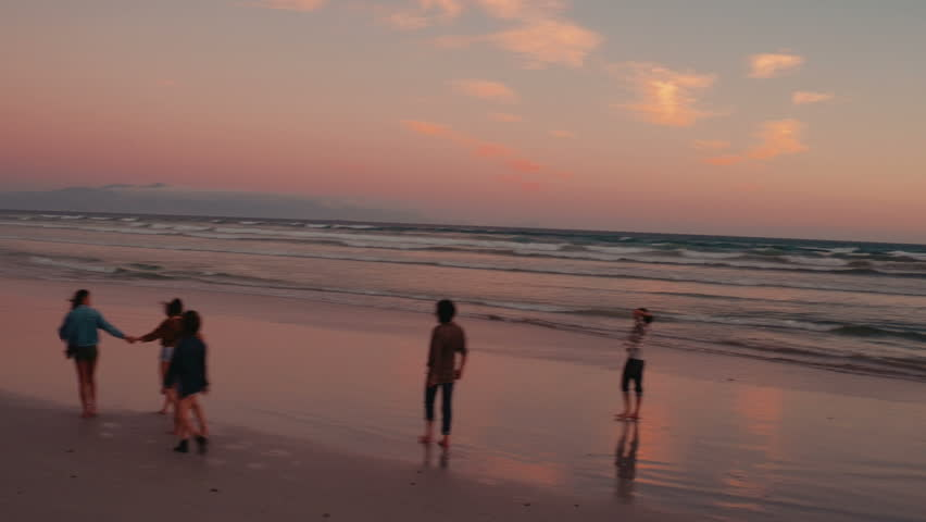 Group of teen friends enjoying a nice walk at beach on sunset. Aerial view  from drone flying over.