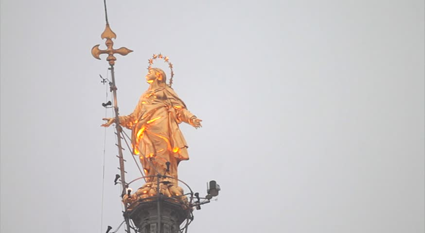 Famous gold statue located on top of the Cathedral dome of Milan, Italy