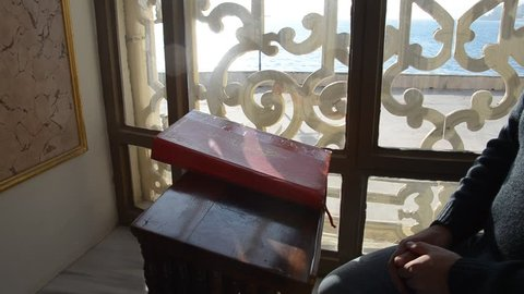 Unknown man in the Ortakoy Mosque a read Quran in Istanbul,  Ortakoy mosque was made in 1856.