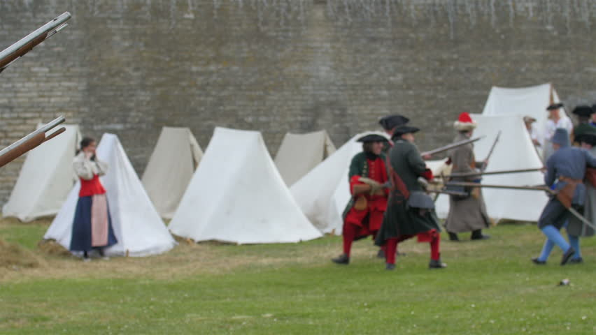 Men in medieval soldier customes walking by holidng guns and spears in the festival play