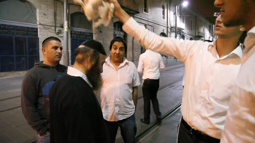 JERUSALEM - OCTOBER 06: Orthodox Jew swings a live chicken over one's head three times during Kapparot, a Jewish ritual practiced by some Jews on the eve of Yom Kippur on October 06 2011 Jerusalem, Israel.    Shutterstock HD Video #1527902
