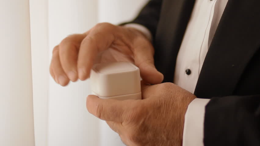 Old man open white box with two wedding rings and look at them.Closeup.