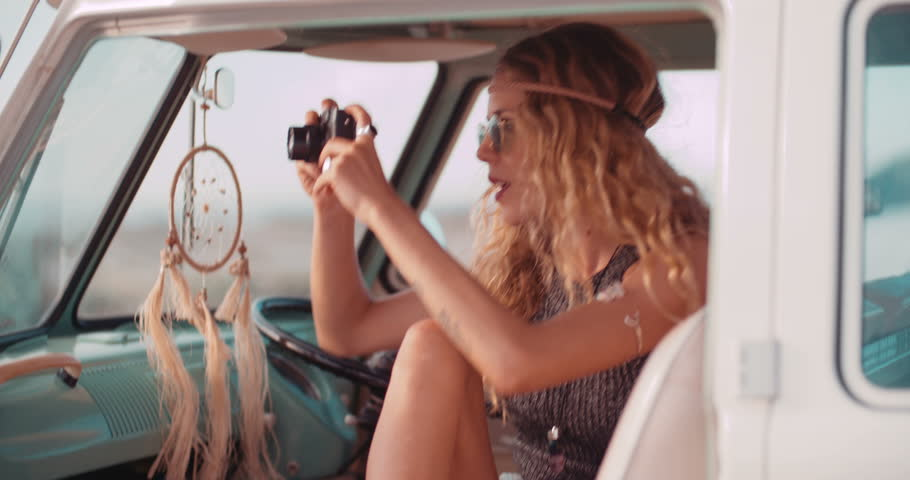 Road Trip Blonde Boho girl taking a photo of the sunset from front seat of retro van parked on a sandy beach