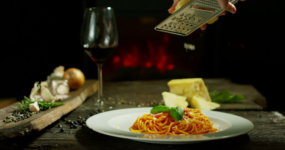 beautiful italian pasta composition in old traditional cottage with fireplace and relax atmosphere with chef garnish plate with parmesan cheese and basil leafs