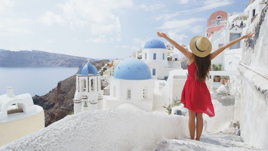 Tourist with arms outstretched in joy in Santorini. Young woman is wearing red dress and sunhat. She is enjoying Europe vacations on the famous Greek island sightseeing visiting travel destination.