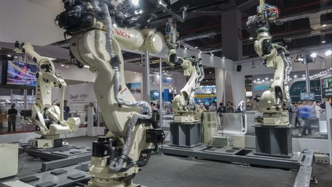 SHANGHAI, CHINA - NOVEMBER 2015: Time lapse of production robots assembling cars at a modern technology trade show in Shanghai, China