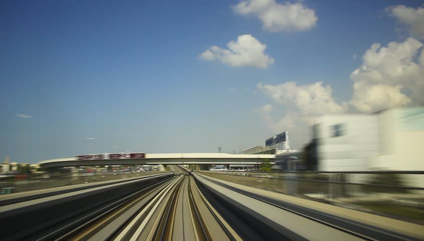 FPV ride at elevated railway, driver cabin view, oncome train sweep past. Dubai Metro rush along overground rails, low rise building around, motion blur, smooth time lapse. Nice blue sky, white clouds