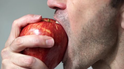Closeup of a unshaven man eating an apple