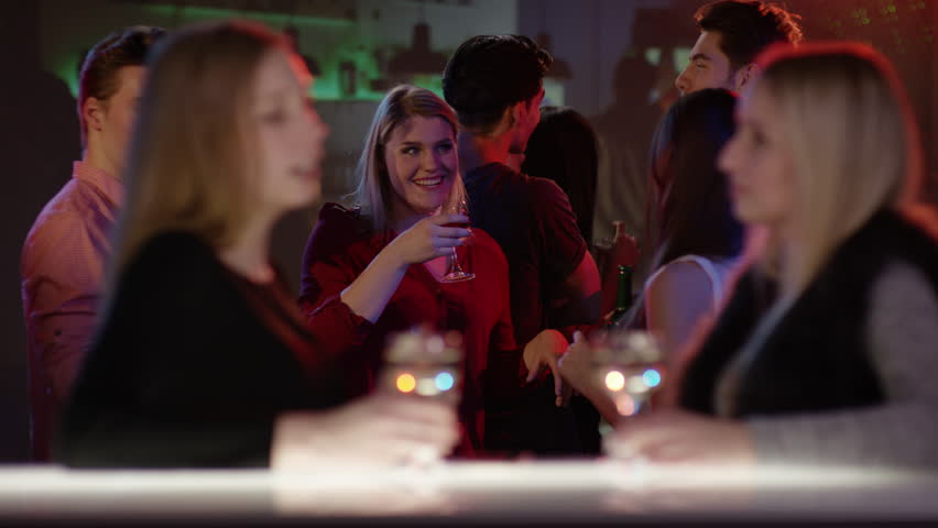 Two attractive girls at bar in club talking and raising their glasses   Shutterstock HD Video #15369562