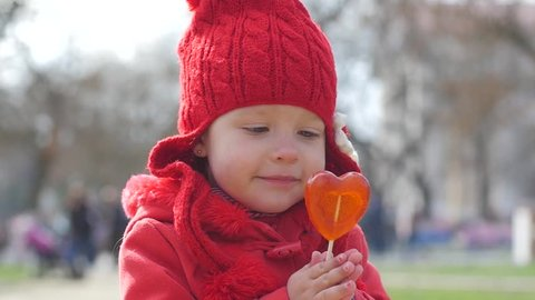 Little girl funny licking a lollipop in the shape of heart in slow motion