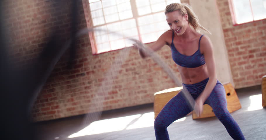 Young adult girl practising battle rope exercise during a crossfit workout at the gym