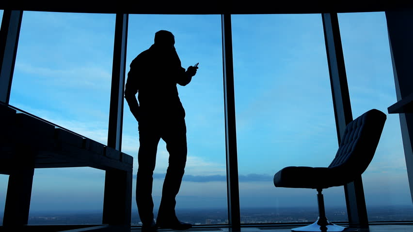 Silhouette of businessman standing with smartphone by window in the office against the sky in the evening, 4K  #15394360