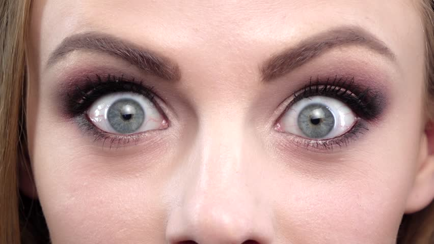 Beautiful girl with bright makeup in amazement. Close up. Slow motion